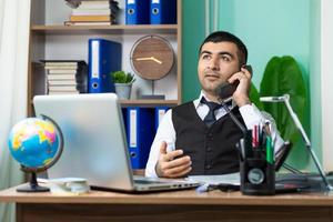 junger Mann, der im Büro am Telefon spricht