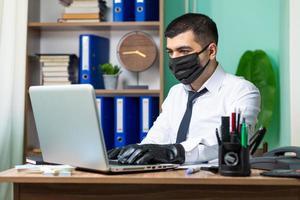 junger Geschäftsmann, der auf Laptop mit schwarzer medizinischer Schutzmaske arbeitet foto