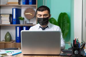 junger Geschäftsmann mit schwarzer medizinischer Schutzmaske foto