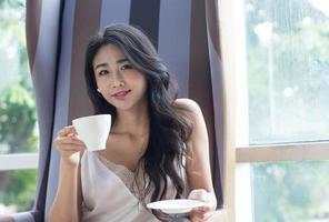 asiatische Frau nippt an Kaffee