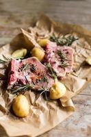 rohes Fleisch mit Kartoffeln und Kräutern auf Holztisch foto