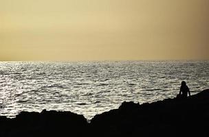 Silhouette der Person, die am Ozeanufer sitzt foto