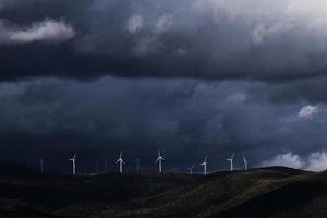 Windkraftanlagen auf Hügel unter schweren Wolken
