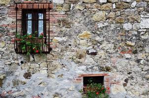 schwarze hölzerne Fensterscheiben auf Kopfsteinpflasterwand