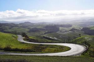 kurvenreiche Straße durch grünes Grasfeld
