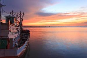 Fischerboot am Strand bei Sonnenuntergang foto