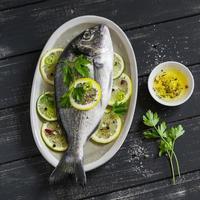 frischer Dorado Fisch mit Zitrone und Gewürzen foto