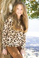 junges schönes lächelndes Mädchen im Leopardenmuster-Pullover im Freien foto