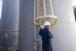 Mann klettert Leiter in Fabrik foto