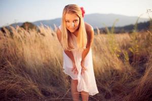 blondes Mädchen im weißen Kleid, das Augenkontakt herstellt