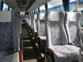 Leere Buspassagiersitze mit Sicherheitsgurt und Kopftuch