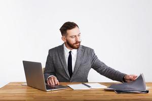 Geschäftsmann arbeitet am Schreibtisch auf weißem Hintergrund