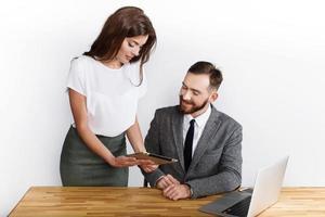 Geschäftsfrau und Mann teilen Ideen auf einem Tablet am Schreibtisch