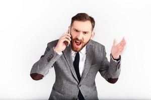 wütender Mann im grauen Anzug telefoniert