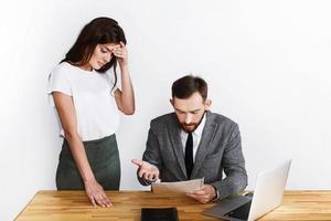 müde Frau steht neben Geschäftsmann, während er wütend auf Papierkram aussieht