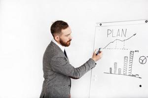 Mann gekleidet im Büroanzug schreibt auf Grafik auf weißem Hintergrund