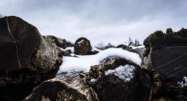 gehacktes Brennholz mit Schnee bedeckt