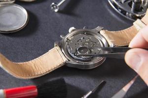 Uhrmacher mit Pinzette auf Uhr foto
