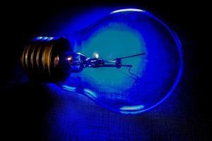 einzelne Glühbirne von hinten von blauem Licht beleuchtet
