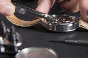 Nahaufnahme des Uhrmachers, der eine Batterie ersetzt foto