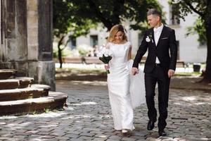 Der Bräutigam hält die Hand der Braut, während er auf dem Kopfsteinpflasterweg geht foto