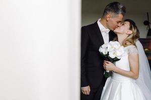 Bräutigam küsst Braut in einem Hotelzimmer