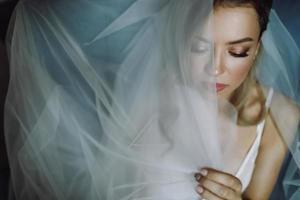 atemberaubende blonde Braut mit tiefen Augen unter blauem Schleier versteckt