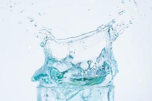 Wasserspritzer in einem gläsernen weißen Hintergrund
