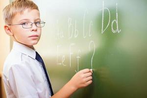 Schuljunge schreibt englisches Alphabet mit Kreide an die Tafel foto