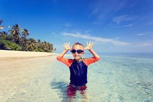 kleiner Junge, der Spaß am tropischen Strand hat