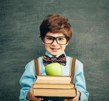 junger männlicher Student, der Bücher und Apfel anbietet foto