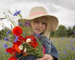 glückliches kleines Mädchen mit einem Strauß Wildblumen.