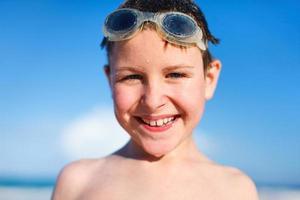 glücklicher Junge in der Schutzbrille am Strand