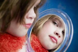 kleines Mädchen, das einen Spiegel schaut