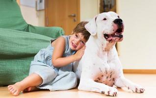 kleines Mädchen, das weißen Hund umarmt