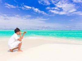 Junge mit Teleskop am Strand