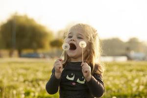 Kind, das mit Löwenzahnblume auf Gras im Feld spielt