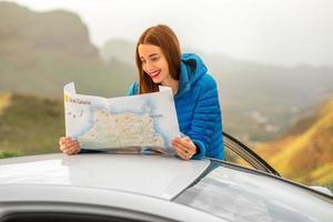 weibliche Reisende mit Tourenkarte in der Nähe des Autos