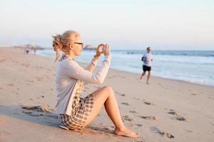 Frau, die Foto am Strand macht