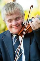 Nahaufnahmeporträt des behinderten Jungen mit Geige. foto