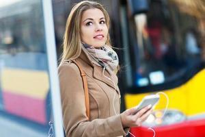 Frau wartet an der Bushaltestelle foto