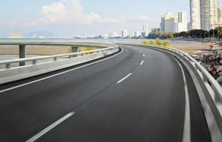 Autobahnüberführungs-Bewegungsunschärfe mit Stadthintergrund.