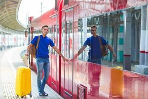 junger Mann mit Gepäck an einem Bahnhof in der Nähe von Aeroexpress