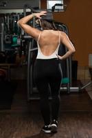 Frau im Fitnessstudio zeigt ihren gut trainierten Körper