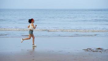 Frau läuft am Strand bei Sonnenuntergang.