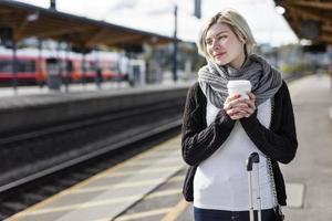 Frau trinkt Kaffee, während sie auf den Zug wartet
