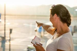 schöne Brünette zeigt ein Flugzeug am Flughafen