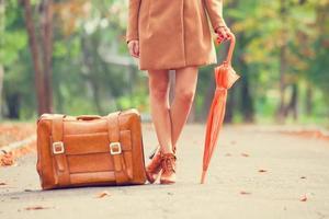 Gril im Mantel mit Regenschirm und Koffer im Park.