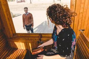 junge Frau winkt im Waggonzug oder in der Straßenbahn und verabschiedet sich