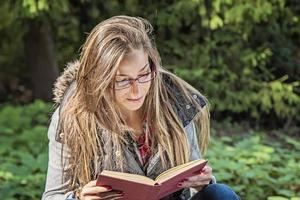 schönes Mädchen, das ein Buch im Herbstpark liest